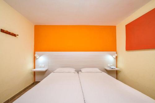 เตียงในห้องที่ Apartamentos Morasol